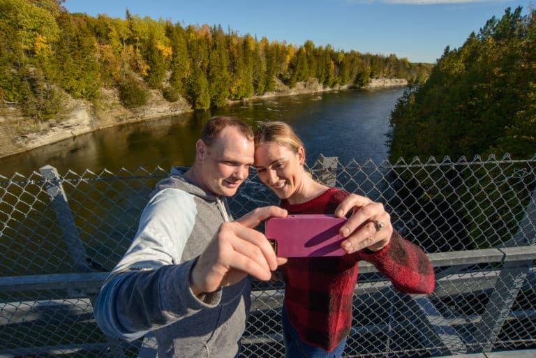 Couple taking photo from the Ranney Gorge Suspension Bridge in Campbelford Trent Hills Ontario